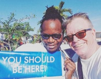 Javia with sign that says 'You Should Be Here' (in Jamaica) with a client